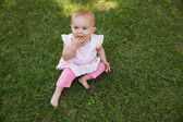 Cute baby sitting on grass at park — Stock Photo
