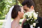 Couple kissing behind flowers in garden — Stock fotografie