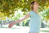 Smiling woman with arms outstretched at park — Stok fotoğraf