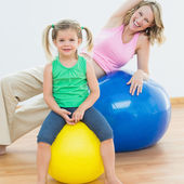 Pregnant woman exercising with daughter — Stock Photo