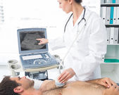 Cardiologist using sonogram on patient — Stock Photo