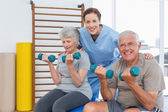 Therapist assisting senior couple with dumbbells — Stock Photo