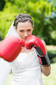 Bride with boxing gloves in garden — Stock Photo