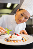 Concentrated female chef garnishing food — Stock Photo