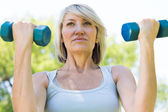 Woman lifting dumbbells in park — Stock Photo