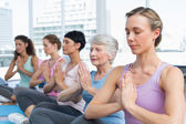 Class sitting with joined hands in a row at yoga class — Stock Photo