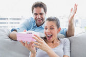 Man surprising his pretty girlfriend with a pink gift on the sofa — Stock Photo