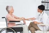 Lekarz mówi starszy pacjenta na wózku inwalidzkim — Zdjęcie stockowe