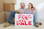 Happy couple sitting on floor with sold sign — Stock Photo