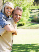 Couple enjoying piggyback ride in park — Stock Photo