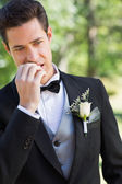 Groom biting nails in garden — Stock Photo