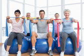 Class holding exercise belts while sitting on fitness balls — Stock Photo