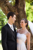 Happy newlywed couple standing in park — Stok fotoğraf
