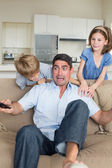 Children scaring father watching television — Stock Photo