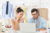 Fashion designers using laptop in studio — Stock Photo