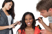 Assistants applying make-up to model — Stock Photo