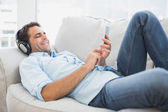 Happy handsome man lying on sofa using tablet and listening to music — Stock Photo