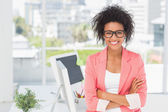 Casual female artist with arms crossed at bright office — Stock Photo