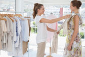 Saleswoman assisting woman with clothes — Stockfoto