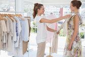 Saleswoman assisting woman with clothes — Zdjęcie stockowe