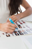 Editor working at desk marking a contact sheet — Stock Photo