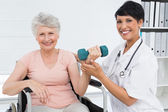 Physiotherapist assisting senior woman to lift dumbbell — Stock Photo