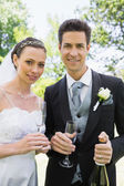 Newlywed couple having champagne — Stockfoto
