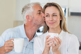 Smiling man giving his partner a kiss on the cheek — Stock Photo
