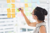 Designer writing on sticky notes on window — Stock Photo