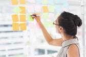 Designer writing on sticky notes on window — Stock Photo