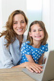 Girl and mother using laptop — Foto Stock