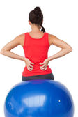 Rear view of a fit young woman sitting on exercise ball — Stock Photo