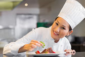 Smiling female chef garnishing food in kitchen — Stock Photo