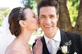 Bride kissing groom on cheek — Stock Photo