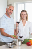 Happy couple making dinner together smiling at camera — Stock Photo