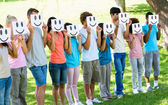 Friends holding smileys in front of faces — Stock Photo