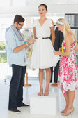 Fashion designers adjusting dress on model — Stock Photo