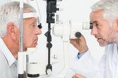 Optometrist doing sight testing for senior patient — Stock Photo