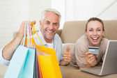 Happy couple shopping online on the couch — Stock Photo