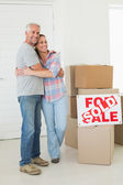 Happy couple standing and hugging beside sold sign — Stock Photo