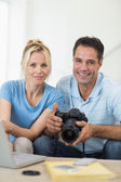 Couple with camera and laptop — Stock Photo