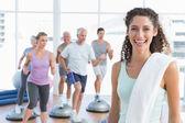 Cheerful woman with people exercising at fitness studio — Stock Photo