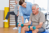Female therapist assisting senior man with dumbbells — Stock Photo