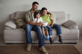 Father and sons watching tv — Stock Photo