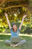 Cheerful woman with laptop raising hands at park — Stock Photo