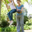 Happy mother swinging daughter at park — Stock Photo #42920099