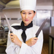 Cook holding knives in kitchen — Stock Photo #42920547