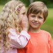 Girl whispering secret into boy's ear — Stock Photo #42920699
