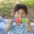Happy boy holding block alphabets as 'learn' at park — Stock Photo #42920789