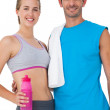 Portrait of a sporty couple with water bottle and towel — Stock Photo